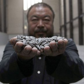 Chinese artist Ai Weiwei poses for a photograph with his new installation entitled 'Sunflower Seeds', at its unveiling in the Turbine Hall at the Tate Modern gallery, in London October 11, 2010. REUTERS/Stefan Wermuth (BRITAIN - Tags: ENTERTAINMENT)