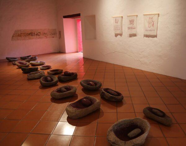 Tania Candiani, La Molienda, instalación de 18 metates y grana cochinilla. Los restos de pigmento son el resultado de una acción en donde 18 mujeres molieron la grana en los metates. Cortesía de la artista
