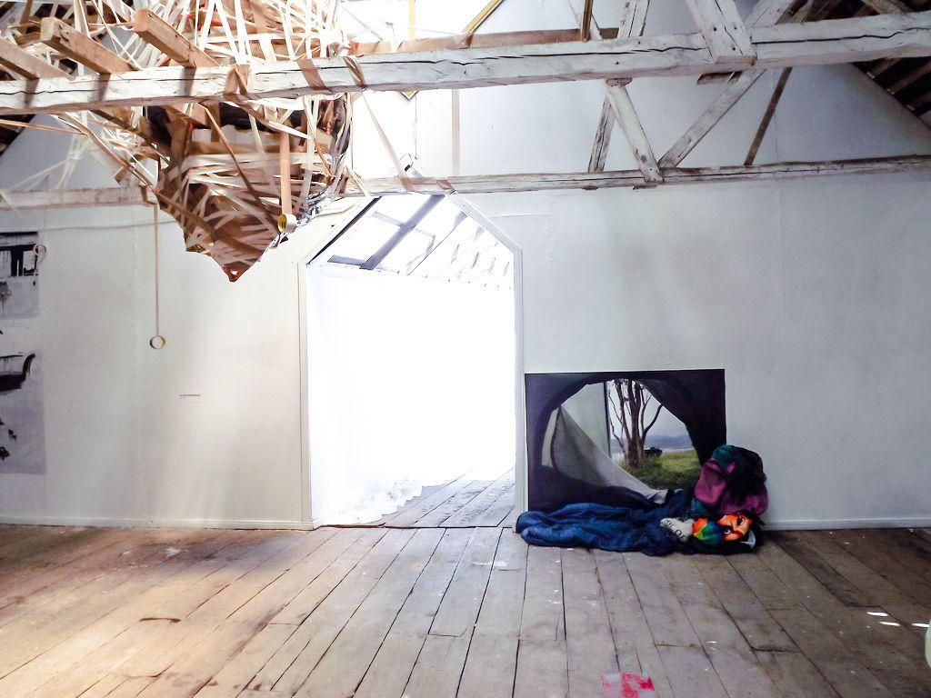 Carlos Silva, Cucao, 2012, impresión sobre papel, 110 x 82 cm, mochila, saco de dormir, toalla de playa, gorro de lana de Chiloé. Vista de la instalación en el Museo de Arte Moderno de Chiloé, Chile. Foto: Cortesía del artista