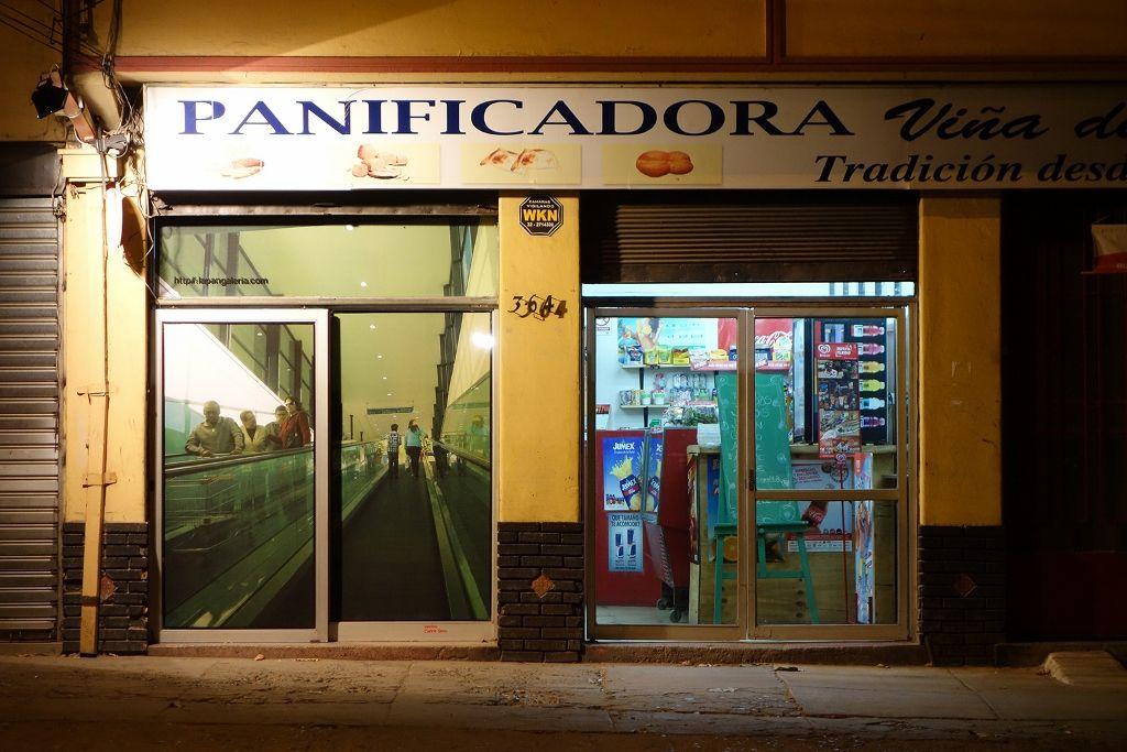 Carlos Silva, Vecino, 2014, 2 fotografías de 230 cm x 210 cm, inyección a tinta montada sobre placa. Intervención en los ventanales tanto interior como exterior de una panadería, con imágenes que generan una proyección arquitectónica posible, en relación a la especulación del valor del suelo. Foto cortesía del artista
