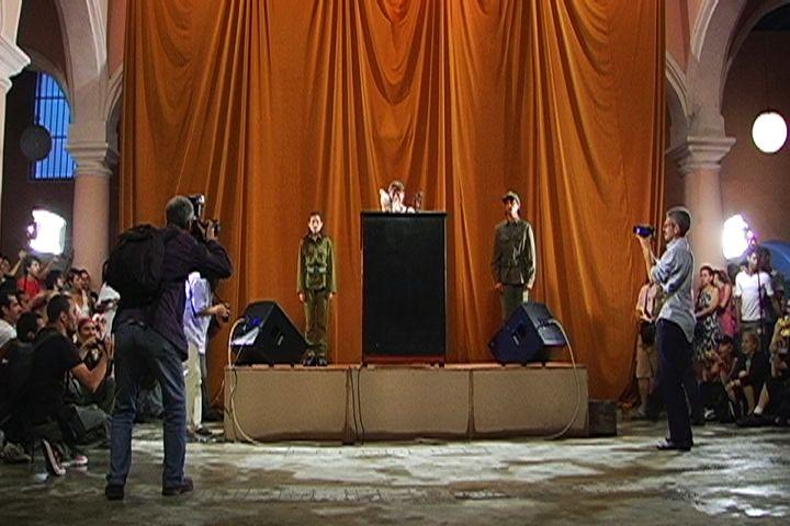 Tania Bruguera, Tatlin Whisper # 6 (versión para La Habana), 2009, arte del comportamiento, escenario, podio, micrófonos, dos parlantes (uno dentro y otro fuera del edificio), dos personas, uniformes militares, paloma blanca, un minuto libre de censura por orador, 200 cámaras desechables con flash. Cortesía Tania Bruguera.