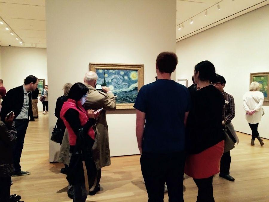 """Personas mirando la obra de Vincent van Gogh titulada """"Noche estrellada"""" (1889), óleo sobre tela, 74 x 92 cm, MoMA. Foto: Paco Barragán"""