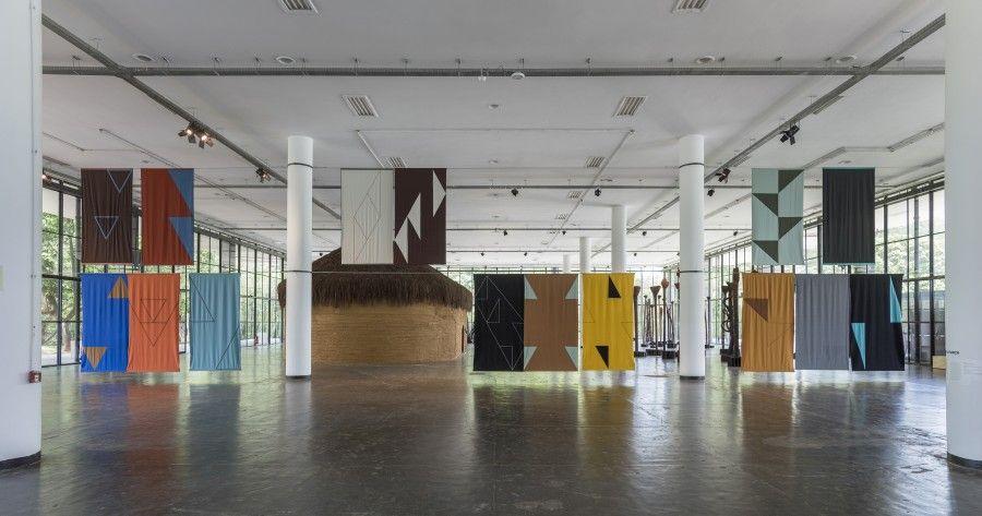 Felipe Mujica, Las universidades desconocidas, 2016, tela de algodón, hilo y lana bordada, 30 paneles de aprox. 295 × 160 cm c/u. Vista de la instalación en la 32° Bienal de São Paulo. Foto: Edouard Fraipont. Cortesía: von Bartha, Londres