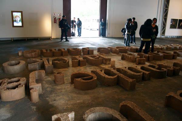 Bernardo Oyarzún, Caligrafía/Caracteres Guaraníes, 2011, instalación con letras hechas de adobe y video retrato. Dimensiones variables