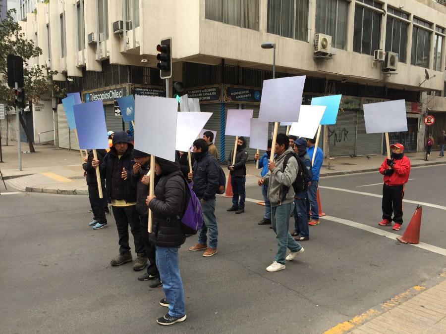 Ciudadanos peruanos residentes en Santiago caminan portando carteles con imágenes del cielo de Perú, instalando así el cielo del país vecino en el paisaje del centro de la capital. Cortesía: GGM