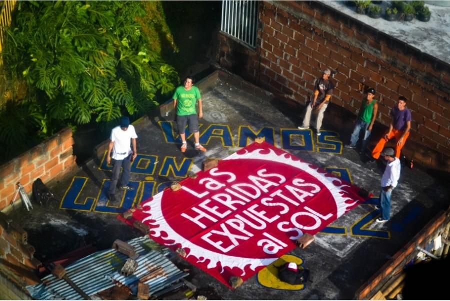 """BijaRi en un techo de Santo Domingo como parte del proyecto de intervención """"Contando con Nosotros"""", 2011. Encuentro Internacional de Medellín (MDE11). Museo de Antioquia."""