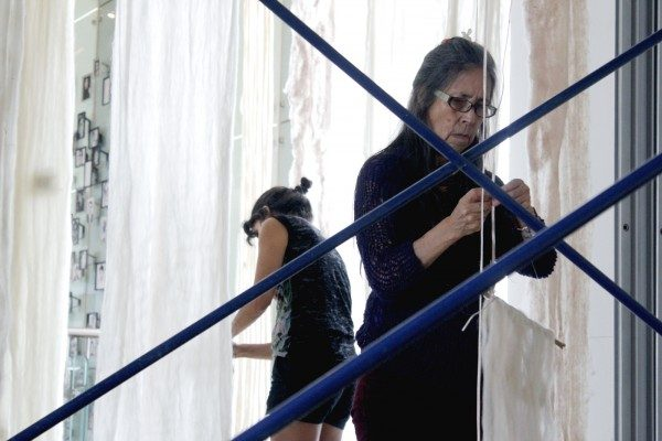 Cecilia Vicuña during the installation of the Artists for Democracy exhibition, in the Museum of Memory and Human Rights, Santiago, 2013. Photo: Macarena Cortés