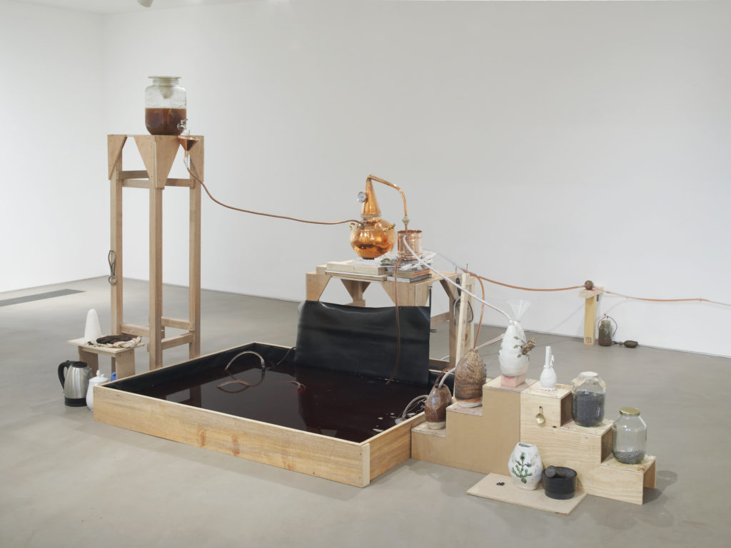 Candice Lin, System for a Stain, 2016. Wood, glass jars, cochineal, poppy seeds, metal castings, water, tea, sugar, copper still, hot plate, ceramic vessels, mortar and pestle, Thames mud, jar, microbial mud battery, vinyl floor. Dimensions variable. Commissioned by Gasworks, London. Courtesy the artist and Ghebaly Gallery, Los Angeles. Installation view, Gasworks, London, 2016. Photo: Andy Keate