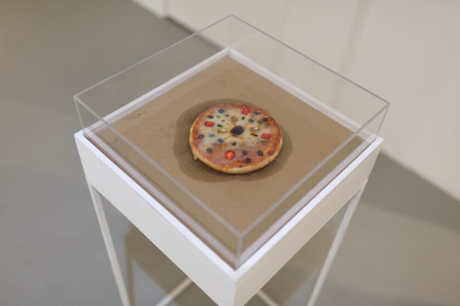 Los Carpinteros, Pizza de gemas, 2016. Pizza de queso, Amatista, Aguamarina, Topacio, Turmalinas, Apatito, Diamante, Ópalo, Rubí y Citrino y vitrina