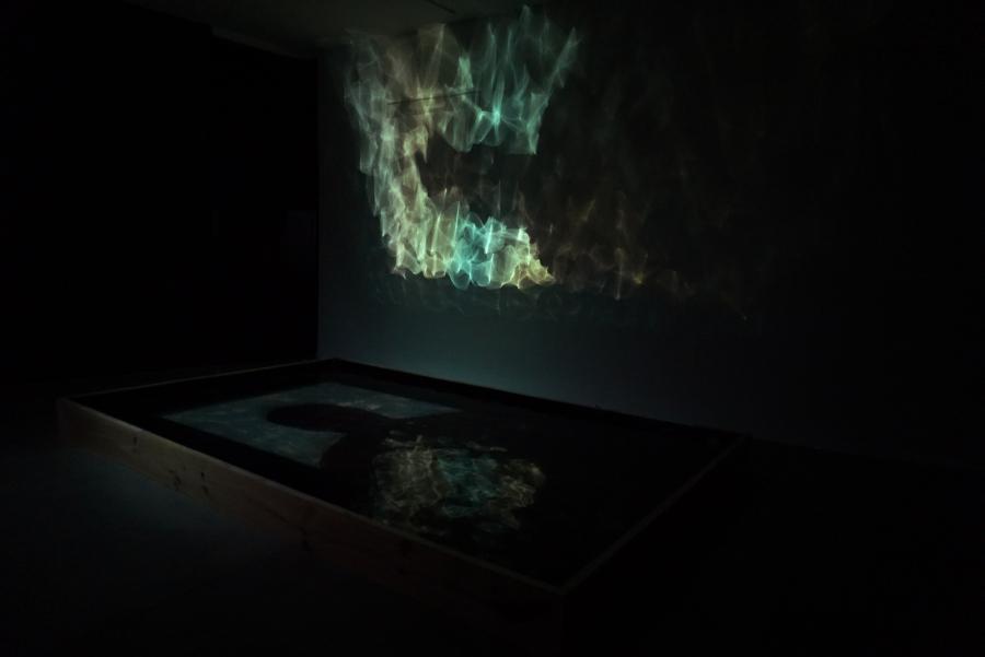 Máximo Corvalán-Pincheira, Aziz, 2017, video ( HD, sonido, loop 9 ́11«), proyección sobre espejo de agua con un mecanismo electromagnético en función del audio de 4 x 2,5 mt. Cortesía del artista