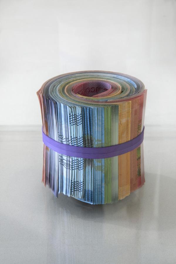 """Adriana Martínez, Al Final del Arco Iris, 2015. Currencies of Costa Rica, Nicaragua, Venezuela, Chile and Brazil, rubber band, 3"""" x 3'. Vista de la exposición Holes in Maps, en 601 Artspace, Nueva York, 2019. Foto cortesía: 601 Artspace /Marie Guex"""