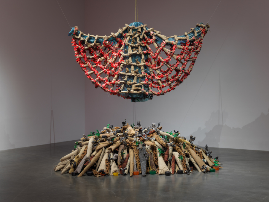 "Nari Ward, Carpet Angel, 1992, carpet, plastic bags, plastic bottles, carpet runner, springs, wood screws, and rope, 230 x 238 x 36 in (584.2 x 604.5 x 91.4 cm). ""Nari Ward: We the People,"" 2019. Exhibition view: New Museum, New York. Photo: Maris Hutchinson / EPW Studio"