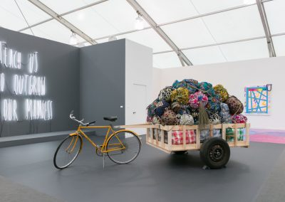 Escultura en neón de Alfredo Jaar y escultura de Barthelemy Toguo en Galerie Lelong. Frieze New York 2019. Foto: Mark Blower. Cortesía: Mark Blower/Frieze