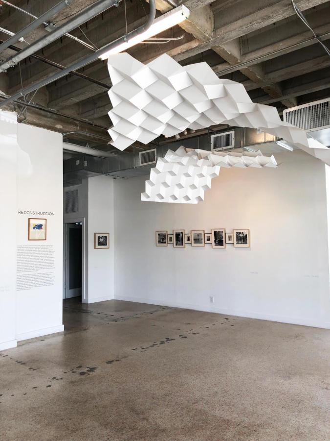 """Arriba: Iván Castillo, de la serie Los Manachos, 2018. Al fondo: fotografías de Alfredo Cortina Vista de la exposición """"Reconstrucción"""" en META Miami, 2019"""