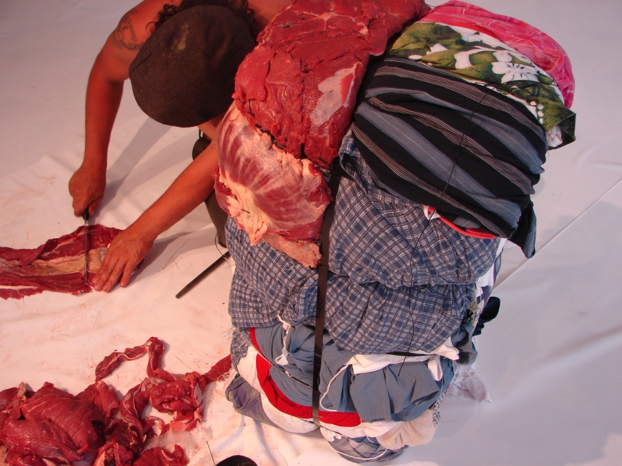 """Jorge de León, In-Out, 2006, parte de la muestra """"Migraciones. Cielo al Revés"""". Performance (cubrir un fardo de ropa americana de desecho con carne). Cortesía del artista"""