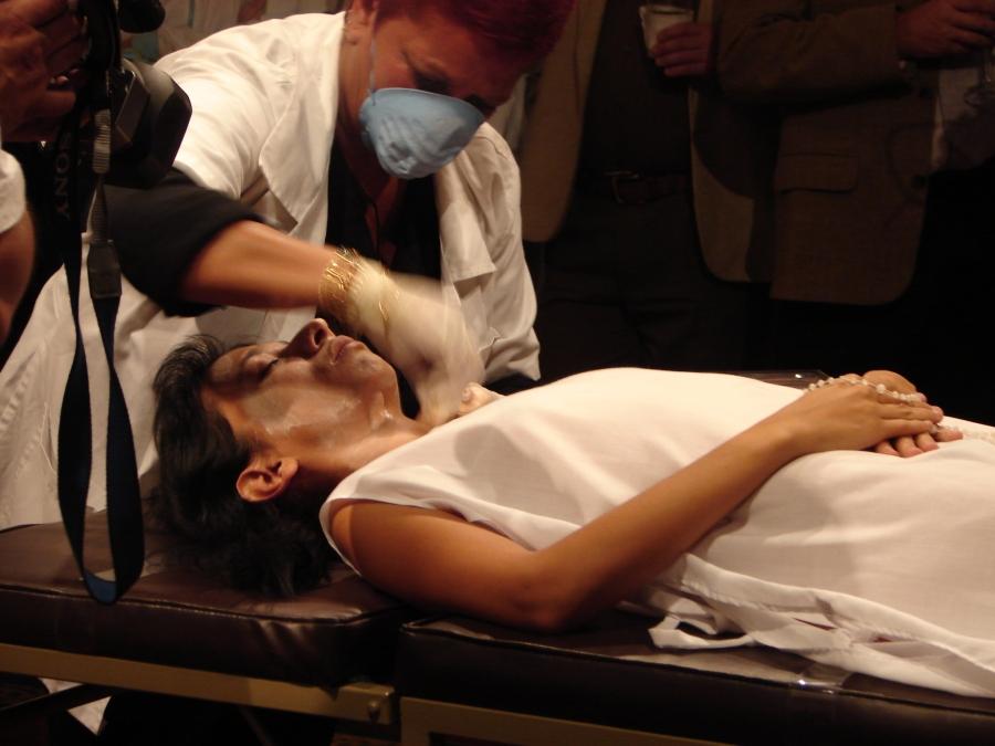 """Regina José Galindo, Tanatosterapia, 2006, parte de la muestra """"Migraciones, cielo al revés"""". Performance (una experta en maquillaje de cadáveres maquilla a la artista). Cortesía de la artista"""