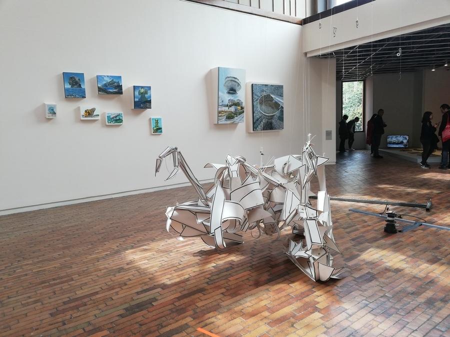 """Obras de Pedro Gómez Egaña (escultura al frente) y Adalberto Calvo (al fondo) en """"Universos desdoblados"""", curaduría de La Usurpadora para el 45 SNA, MAMBO, Bogotá, 2019. Foto cortesía de 45 SNA"""