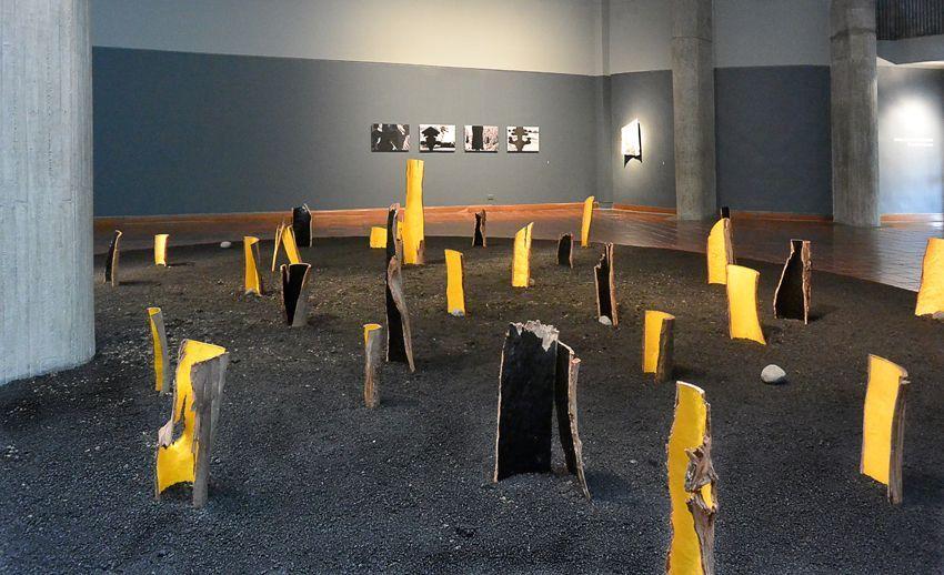 Nicolás Gómez, Parque estacionario, instalación en el Museo de Arte de Pereira, 2015, troncos pintados con pintura de tráfico sobre asfalto. Cortesía del artista