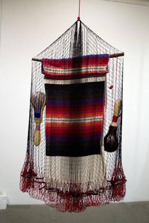 Carolina Caycedo, Cosmotarraya Yaqui, 2016, red de pesca artesanal teñida a mano, pesas de plomo, palo de madera, poncho de algodón, maracas de cuero, chile seco, 90 x 55 x 10 cm. Cortesía del Solomon R. Guggenheim Museum, Nueva York, e Instituto de Visión, Bogotá
