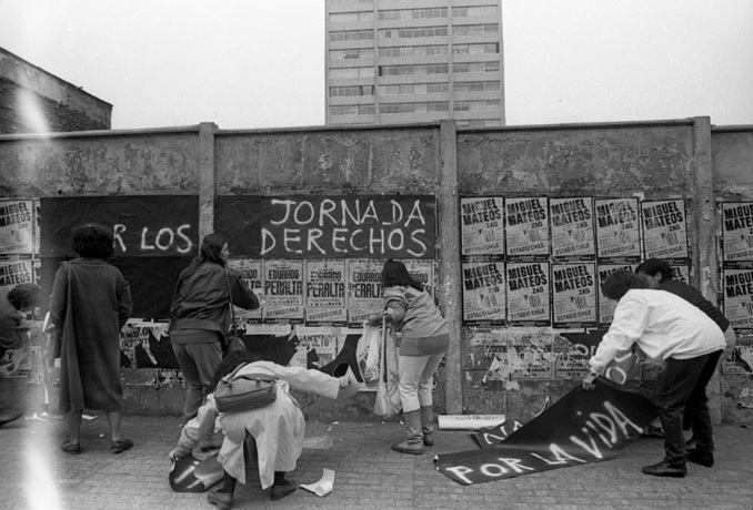 Kena Lorenzini (fotógrafa chilena), Agrupación Mujeres por la Vida pegando carteles en Avenida Libertador General Bernardo O'Higgins, 1988, Jornada Nacional por los Derechos Humanos. Cortesía de Kena Lorenzini