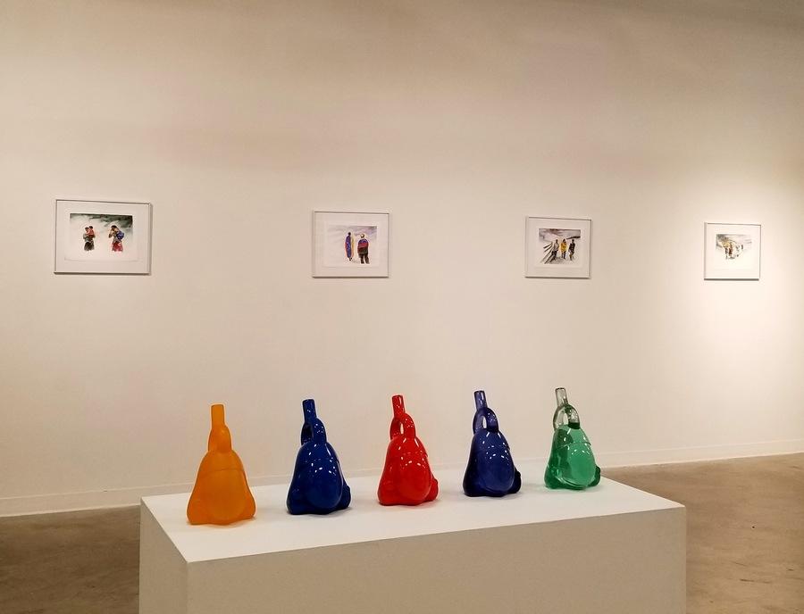 """Al frente: esculturas de Ana de Obregoso. Al fondo: acuarelas de Nohemí Pérez. Vista de la exposición """"Estéticas migratorias"""", en la galería de la George Mason University, Washington D.C, 2019. Cortesía: RoFA Projects"""