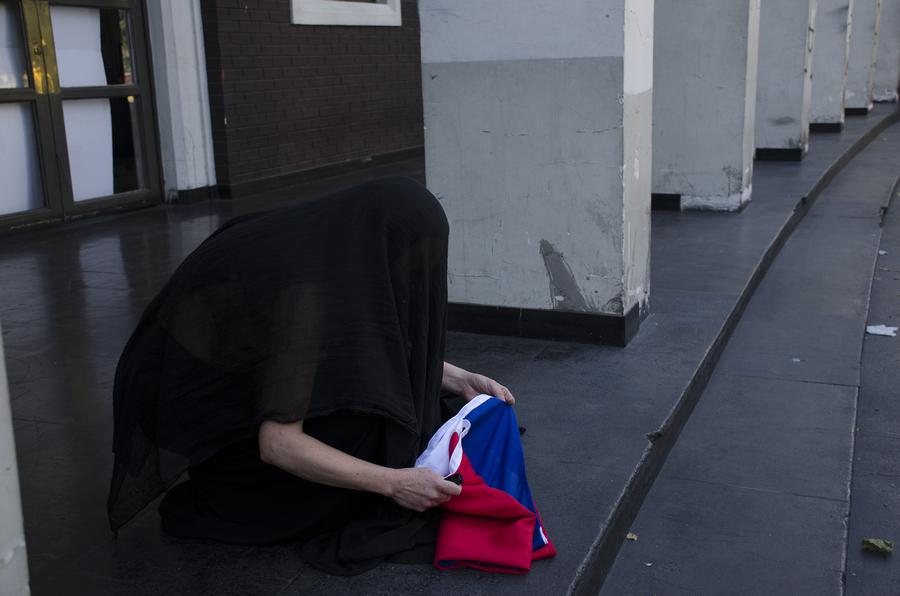 Janet Toro, La bandera en los tiempos de la indignación, 2019. Performance en la fachada del edificio del Sernatur, Santiago de Chile. Foto: Marucela Ramírez M.