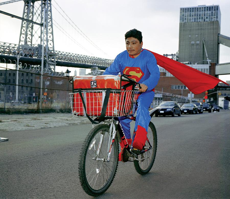 """Dulce Pinzón, Superman (de la serie """"La verdadera historia de los superhéroes""""), 2005. Noé Reyes, originario del estado de Puebla. Trabaja como repartidor en Brooklyn, NY. Manda 500 dólares a la semana. Impresión digital, 210.8 × 279.4 cm. Cortesía de la artista"""